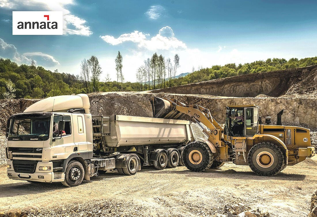 annata-front-loader-filling-a-tractor-trailer-against-a-quarry-background